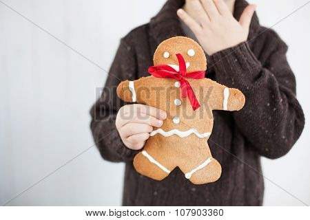 child holding Gingerbread man - boy biting gingerbread people