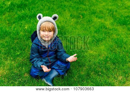 Cute kid resting outdoors, sitting on a lawn