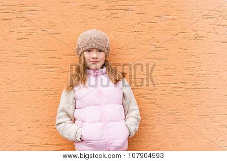 Outdoor portrait of a cute little girl wearing warm knitted beige beret and warm pink coat