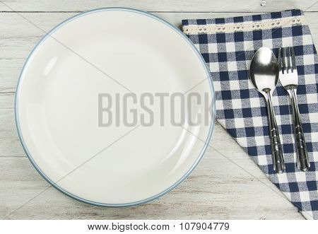 setting empty plate and spoon,fork with tablecloth on white wooden table.