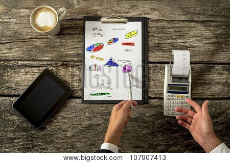 Top View Of Male Accountant Doing Calculations Using Adding Machine As He Doodles Various Graphs, Ch