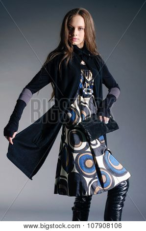fashion model holding little purse posing â??gray background