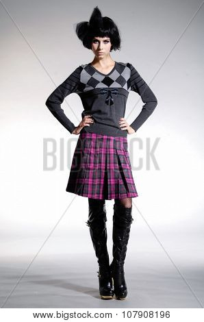 Full body fashion model in fashion dress with hat posing on light background