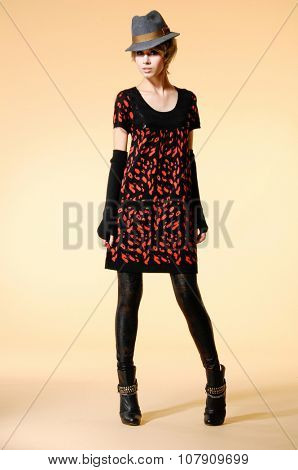 full-length fashion model in gloves with hat posing