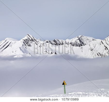 Mountains In Mist And Warning Sing On Ski Slope