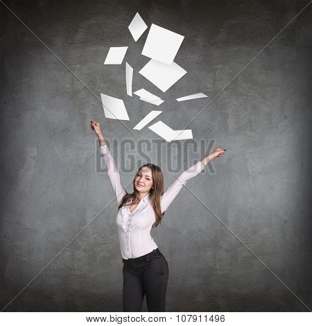 Young business woman throws up paper sheets.