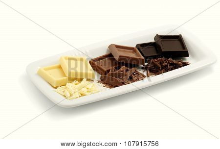 Dark chocolate, milk chocolate and white chocolate shavings on a white background