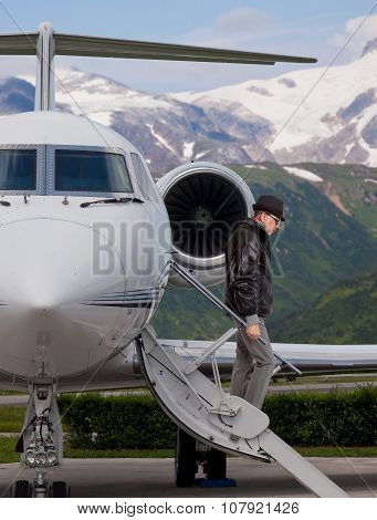 Elegant man descending the stairs from a private jet
