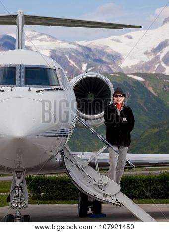 Handsome man on the steps of a private jet