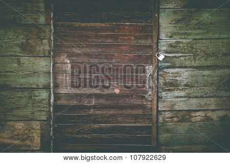 Wooden door with lock and green wall of the old barn in a vintage style
