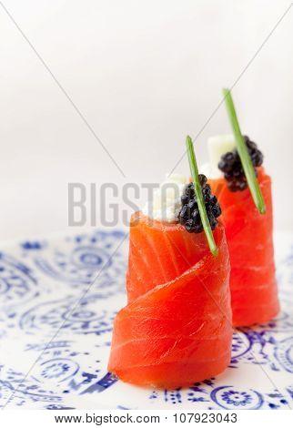 Smoked salmon rolls with cream cheese, black caviar