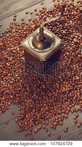 Old vintage bronze coffee mill on spilled roasted hot beans