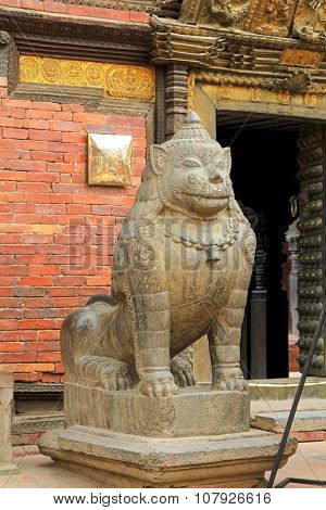 PATAN, NEPAL - APRIL 2014 : Huge stone lion guarding the Sun Dhoka (Golden Gate) at the entrance to Patan Museum in Patan, Nepal on 13 April 2014. Patan Museum is old residential court of Patan Darbar