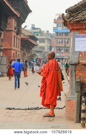 KATHMANDU, NEPAL - APRIL 2014 : A Buddhist monk holding a big silver bowl for tourists and local to donate money in the Durbar Square, Central Kathmandu, Nepal on 13 April 2014.