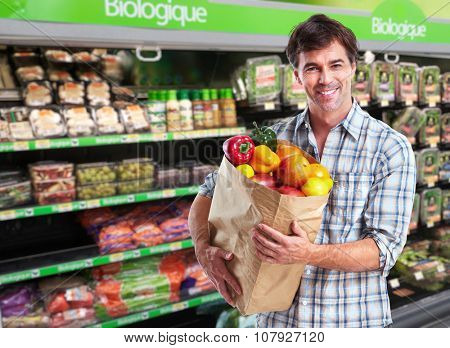 Man with grocery bag of vegetables in a supermarket background.