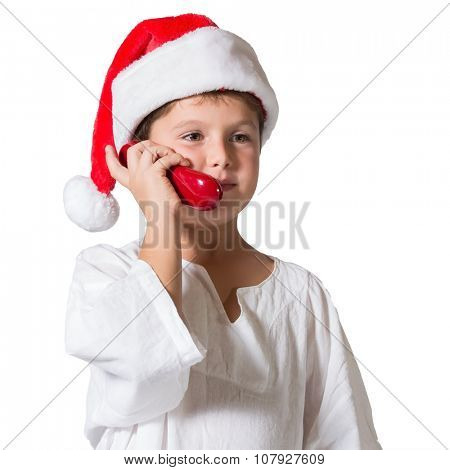 Very beautiful seven year old boy in a red cap. He is talking on the red phone
