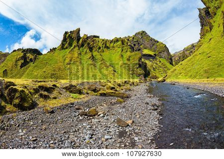 Picturesque lonely canyon Pakgil. Ancient basalt mountains overgrown with a green grass and moss. On a canyon the fast stream flows. Iceland in the summer