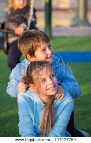 Sister and brother in the same blue jackets play in the playground. Adorable kids