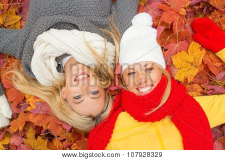Two happy girlfriends laying on the ground