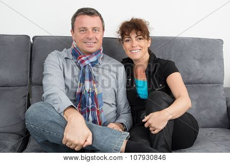 Happy And Lovely Couple On Sofa At Home