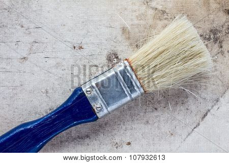 Paintbrush On A Dirty Canvas Surface