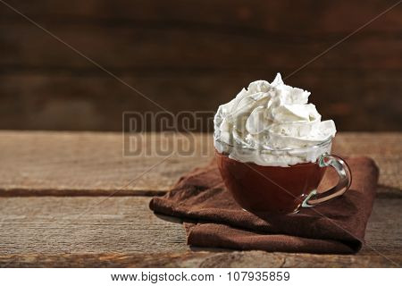 Hot chocolate with whipped cream in mug  on wooden background