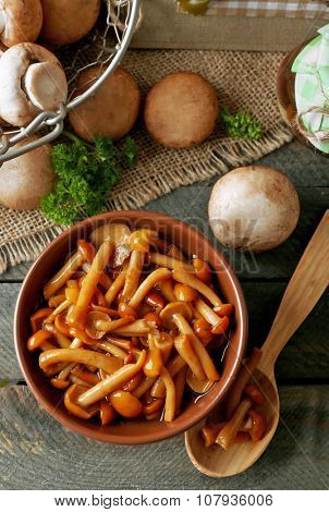Delicious marinated mushrooms in bowl on wooden background