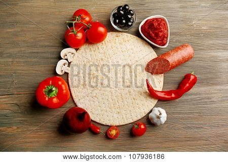 Dough basis and ingredients for pizza in the shape of circle, on the table
