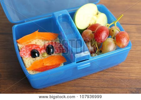 Creative sandwich and fruits in plastic lunchbox on wooden background