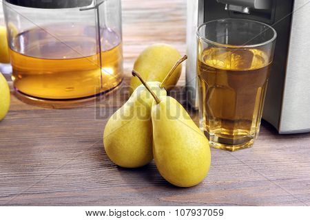 Stainless juice extractor with pears and glass of juice on wooden background, close up