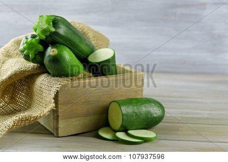 Fresh zucchini in box on wooden background