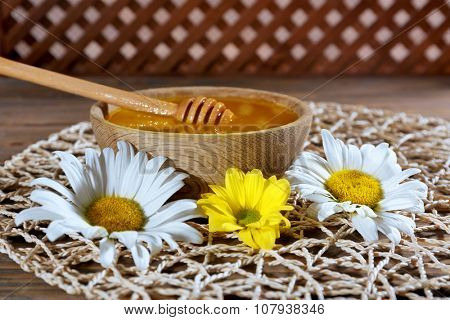 Bowl of honey with wooden dipper and flowers on wicker mat closeup