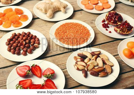 Different products on saucers on wooden table close up