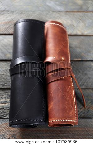 Leather cases on wooden background