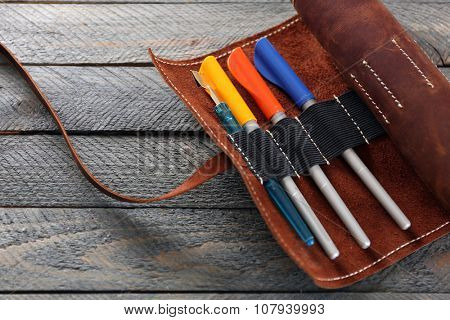 Leather case with items for drawing, on wooden background