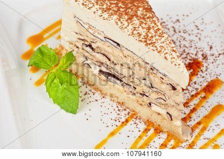 Italian dessert. Cake from ice cream mascarpone cheese chocolate. Decorated with mango sauce.