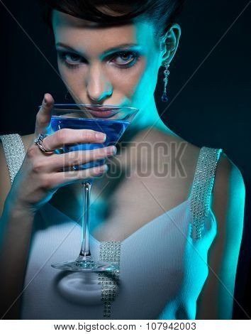 Young woman with martini glass in blue light on dark background. Focus on eyes.