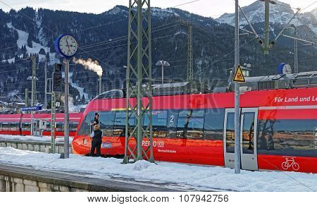 GARMISCH-PARTENKIRCHEN GERMANY - JANUARY 6 2015: Driver of a shiny red train awaiting departure at Garmisch-Partenkirchen train station on a sunny winter day. Bavaria. Germany