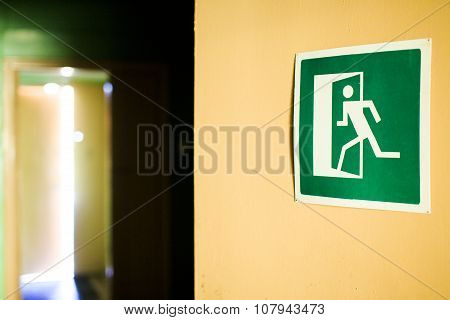 green emergency exit sign on the wall showing the open door in the distance