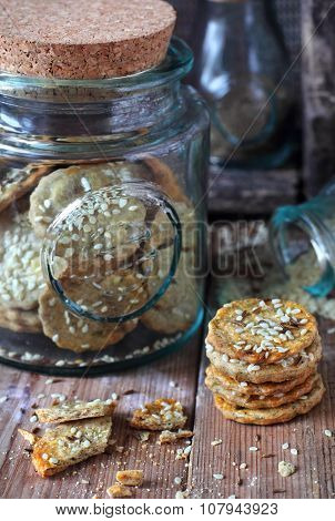 Rye Crackers With Sesame Seeds On A Wooden Background And In A Glass Jar
