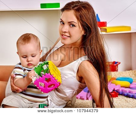 Kid baby boy with mother lying on floor and plying puzzle toy at home.