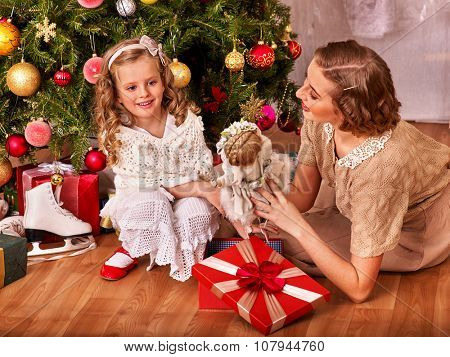 Child with mother receiving  doll gifts under Christmas tree. Vintage style.