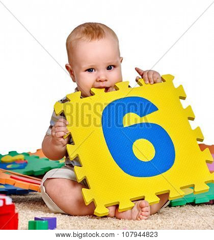 Kid baby boy plying with puzzle toy. Isolated.