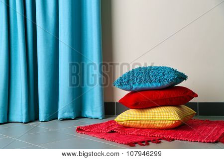 Multicoloured pillows on a carpet in a room