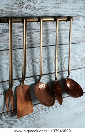 Kitchen utensil of scapula, spoons and fork on wooden background