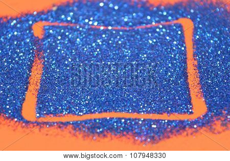 Blurry abstract background with rectangular frame of blue glitter sparkles on red surface