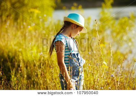 Girl In A Hat Stands Among The Tall Grass