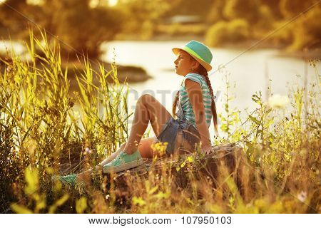 Girl Sitting On The River Bank