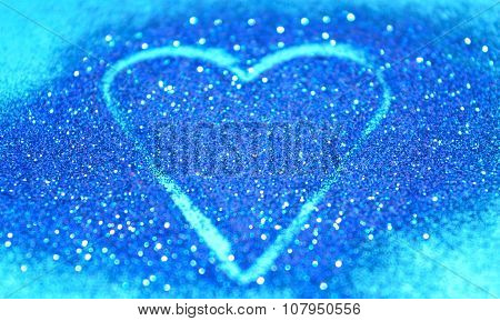 Blurry abstract background with heart of blue glitter sparkle on blue surface