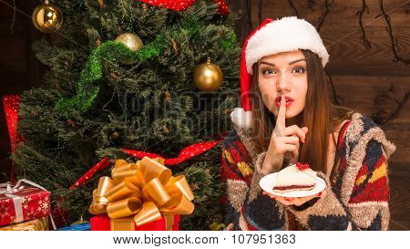Beautiful girl sitting near New Year tree and eating delicious cake